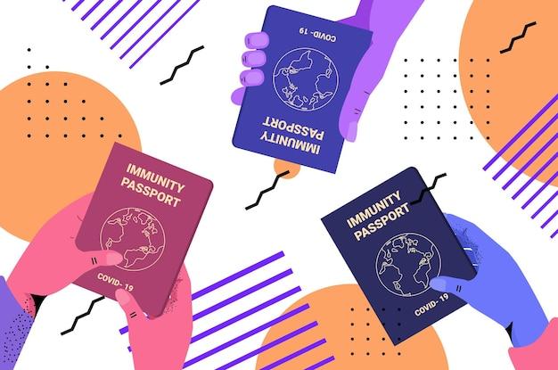 Ludzkie ręce trzymające globalne paszporty odpornościowe wolne od ryzyka ponownej infekcji covid-19 certyfikat pcr odporność na koronawirusa