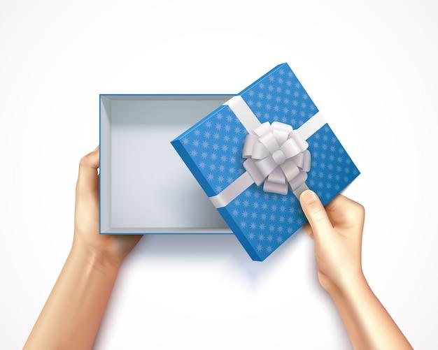 Ludzkie ręki trzyma prezenta pudełka odgórnego widoku realistycznego 3d kwadrata karton z błękitną polki kropką