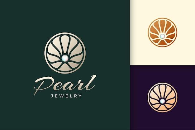 Luksusowe perłowe logo w abstrakcyjnym i okrągłym kształcie reprezentuje biżuterię lub piękno