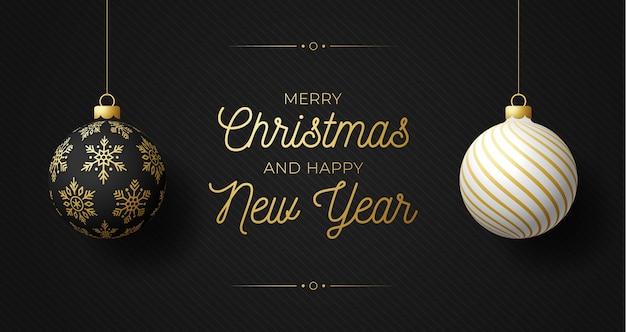 Luksusowy poziomy baner boże narodzenie i nowy rok z dwiema kulkami. kartka bożonarodzeniowa z ozdobnymi czarno-białymi realistycznymi kulkami zawieszonymi na nitce na czarnym nowoczesnym tle. ilustracja.