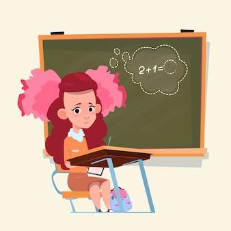Mała uczennica siedzi przy biurku