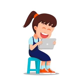 Mała dziewczynka ogląda na tablecie siedząc na krześle