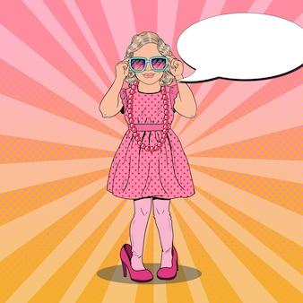 Mała dziewczynka w butach matki i okularach przeciwsłonecznych
