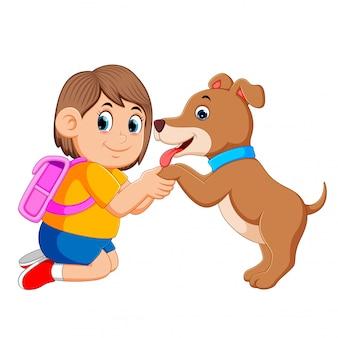 Mała dziewczynka z różową torbą trzymającą stopy psa