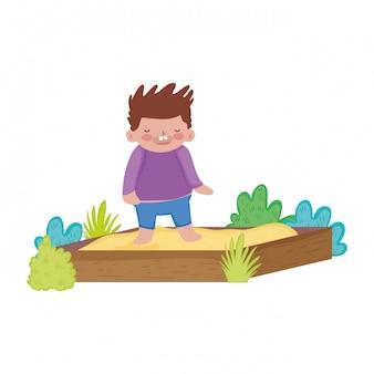 Mała pyzata chłopiec bawić się w piaska pudełku