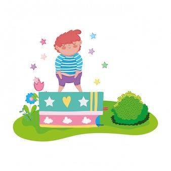Mała pyzata chłopiec z książkami w krajobrazie