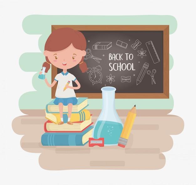 Mała studencka dziewczyna z chalkboard i szkolnymi dostawami