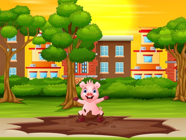 Mała świnia gra kałużę błota w parku miejskim