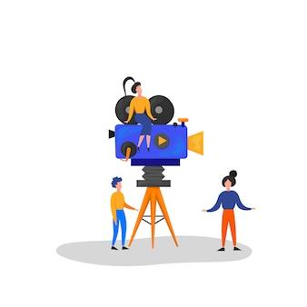 Małe postacie tworzą film. operator używający kamery i personelu z profesjonalnym sprzętem do nagrywania filmu. reżyser z megaphone, people with clapperboard i reel film. ilustracja kreskówka
