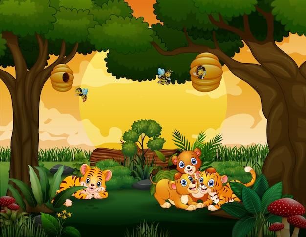 Małe tygrysy i lwy bawiące się w drewnie
