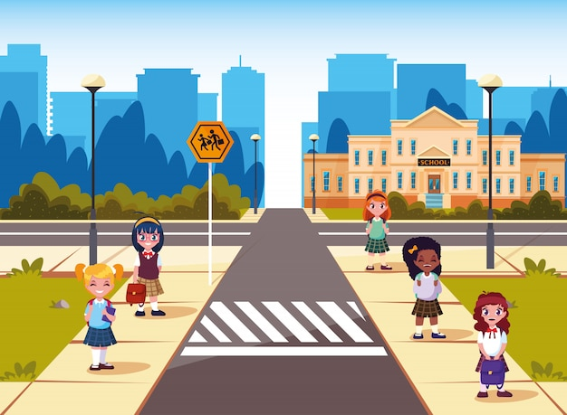 Małe uczennice przed budynkiem szkoły