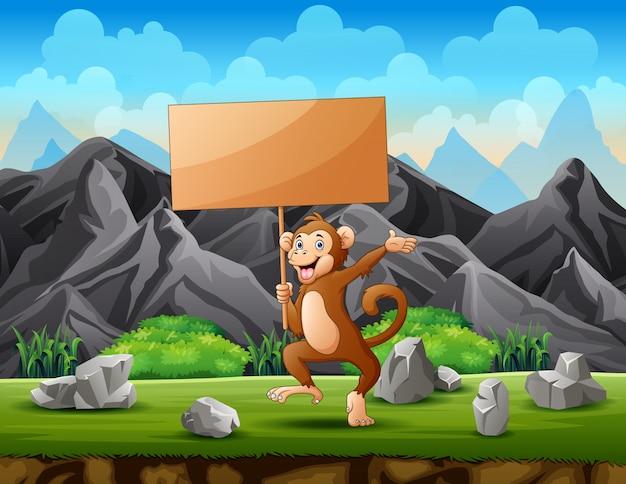 Małpa trzyma drewnianą znak deskę w górze