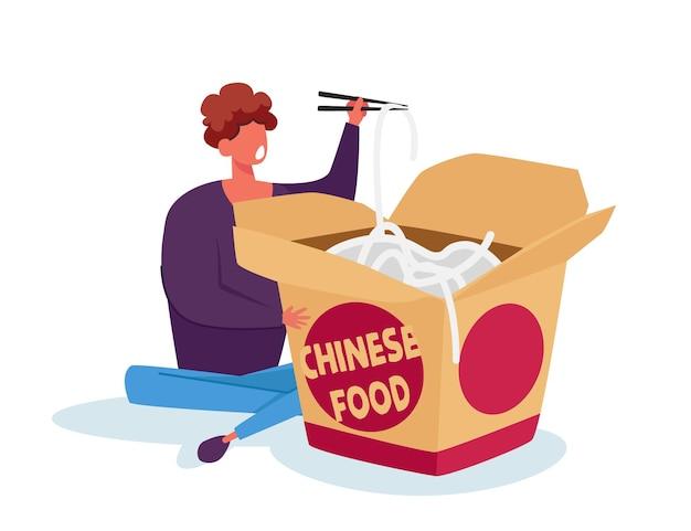 Malutki mężczyzna trzymający drewniane pałeczki w chińskiej restauracji fast food siedzący obok ogromnego pudełka woka na wynos, jedzącego makaron