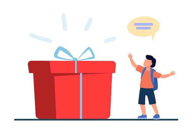 Malutki uczeń stojący obok ogromnego pudełka. teraźniejszość, niespodzianka, ilustracja wektorowa płaski chłopiec. urodziny i wakacje