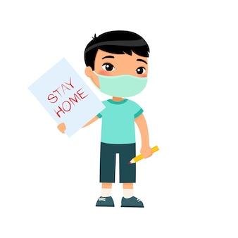"""Mały azjatycki chłopiec z maską na twarz trzymając kartkę ze znakiem """"pobyt w domu"""" śliczny schoolkid z wizerunkiem i ołówkiem w rękach odizolowywać na białym tle. koncepcja ochrony przed wirusami."""