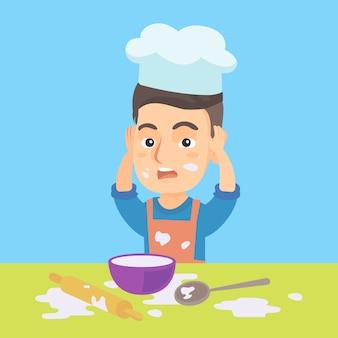 Mały caucasian szef kuchni robi bałaganowi podczas gotowania.