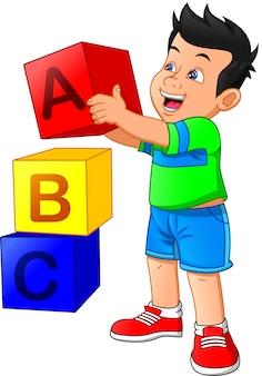 Mały chłopiec bawi się z bloku alfabetu