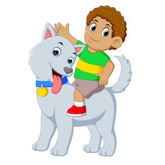 Mały chłopiec jest na wielkim szarym psie do grania