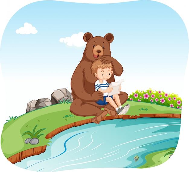 Mały chłopiec siedzi z niedźwiedzia nad rzeką