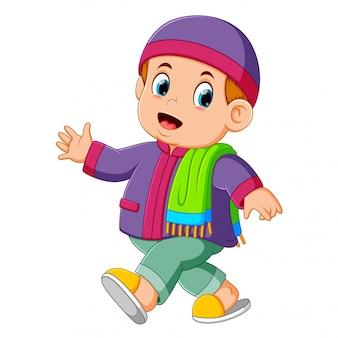Mały chłopiec używa fioletowego kaftana i idzie