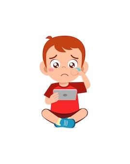 Mały chłopiec używający telefonu komórkowego i płacz