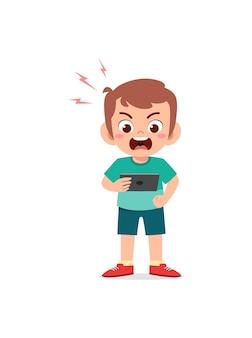 Mały chłopiec używający telefonu komórkowego i zły
