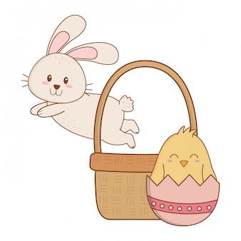 Mały królik i kurczątko z jajkiem malującym w koszu