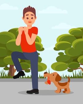 Mały wściekły pies szczeka na człowieka. młody chłopak w sytuacji stresowej. zieleni parkowi drzewa i niebieskie niebo na tle.