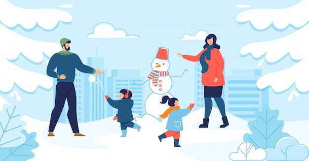 Mama i tata z dziećmi, ciesząc się zimą razem