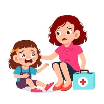 Mama pomaga pierwszej pomocy małej dziewczynce