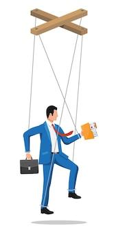 Marionetka biznesmen wisi na linach. ręka lalkarza trzymającego człowieka biznesu. lalka marionetka