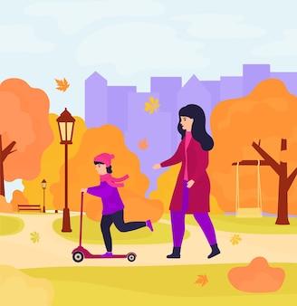 Matka i córka spacerują po jesiennym parku. dziewczyna jeździ na hulajnodze.