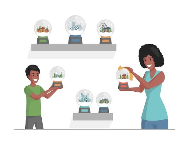 Matka i syn wycierają kurz ze szklanych kulek śniegu