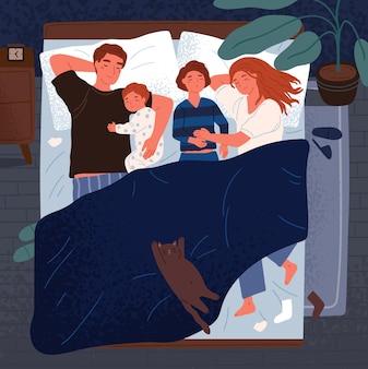 Matka, ojciec i dzieci śpią razem na jednym łóżku. mama, tata i dzieci obejmują się i śpią w nocy