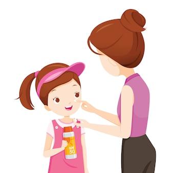 Matka ubrana w krem do opalania na twarzy córki