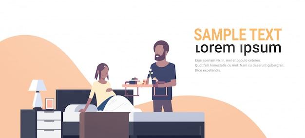 Mąż przynosząc tacę śniadaniową dla żony siedzącej na łóżku mężczyzna serwujący jedzenie szczęśliwej rodziny przyszłych rodziców
