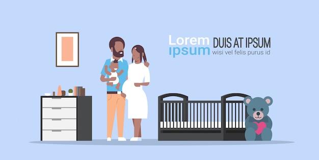 Mąż z ciążą żona trzyma nowonarodzonego syna stojącego w pobliżu rodzicielstwa rodziny szopka