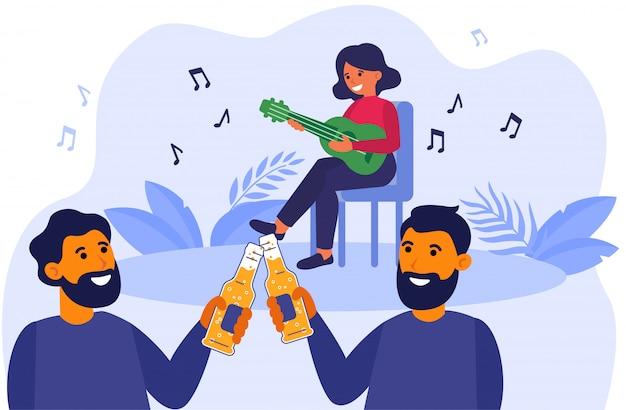 Męscy przyjaciele pije piwo przy akustyka koncertem outdoors