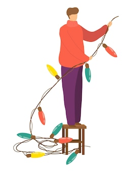 Męska postać trzyma świąteczną girlandę elektryczną