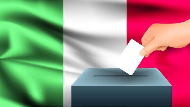 Męska ręka odkłada białą kartkę papieru ze znakiem jako symbolem karty do głosowania na tle flagi włoch. włochy symbolem wyborów