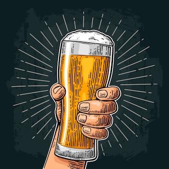 Męska ręka trzyma szklankę piwa. urodzony do picia piwa