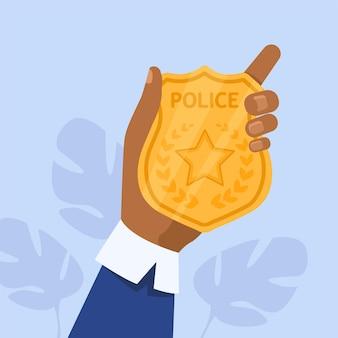 Męska ręka trzyma złotą odznakę policyjną