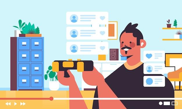 Męski bloger nagrywanie procesu gry blog online transmisja strumieniowa na żywo koncepcja blogowania facet grający w gry wideo wnętrze salonu poziomy portret