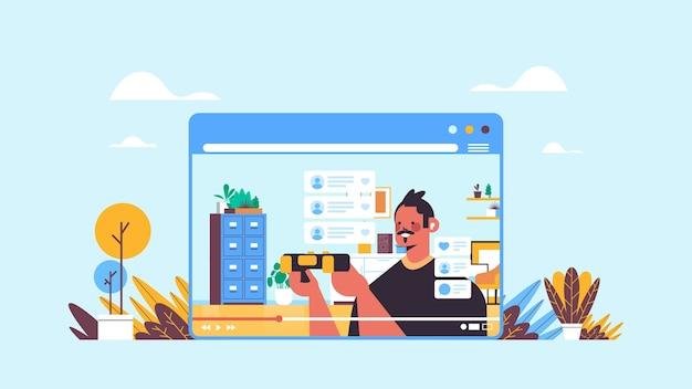 Męski bloger nagrywanie procesu gry blog online transmisja strumieniowa na żywo koncepcja blogowania facet w oknie przeglądarki internetowej grający w gry wideo wnętrze salonu poziomy portret