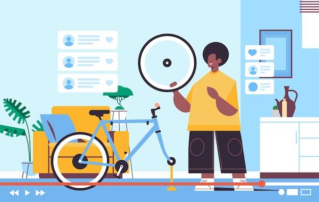 Męski bloger naprawiający nagrywanie roweru online blog wideo transmisja strumieniowa na żywo koncepcja blogowania mężczyzna sprawdzający wady opon warsztat wnętrze poziome