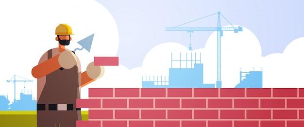 Męski budowniczy używa szpachelka robociarza kłaść ściana z cegieł pracownika w jednolitym murowanie budynku pojęcia budowy terenu tła płaskim portrecie horyzontalnym