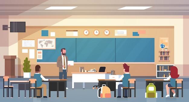 Męski nauczyciel i uczniowie w klasie na lekcji nauczanie w klasie szkolnej