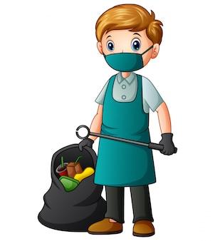 Męski odkurzacz trzymający szczypce i worek na śmieci