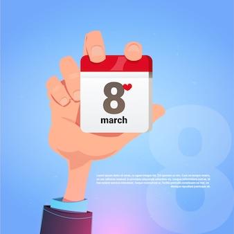 Męskiej ręki trzymającej strony kalendarz z 8 marca data szczęśliwy międzynarodowy dzień kobiet koncepcja wakacje