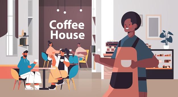 Mężczyzna barista w mundurze pracujący w kawiarni kelner w fartuchu obsługujący kawę dla klientów nowoczesne wnętrza kawiarni poziomej wektorowej